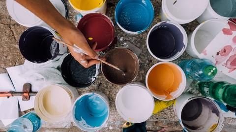 tins-of-paint-and-hand-with-paintbrush